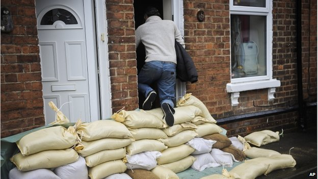 A man climbs over a high pile of sandbags to get into the front door of a house