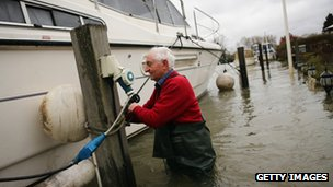 Resident Derrick Foxwell attempts to dislodge his boat that had become stuck on its mooring outside his house the Thames
