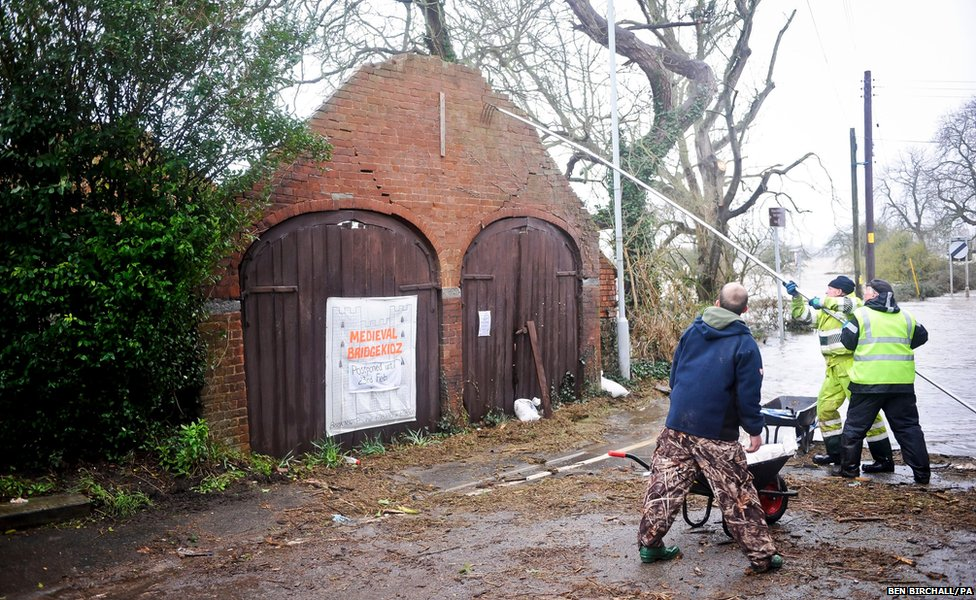 Volunteers try to support a wall which may collapse due to the weather in Burrowbridge, Somerset