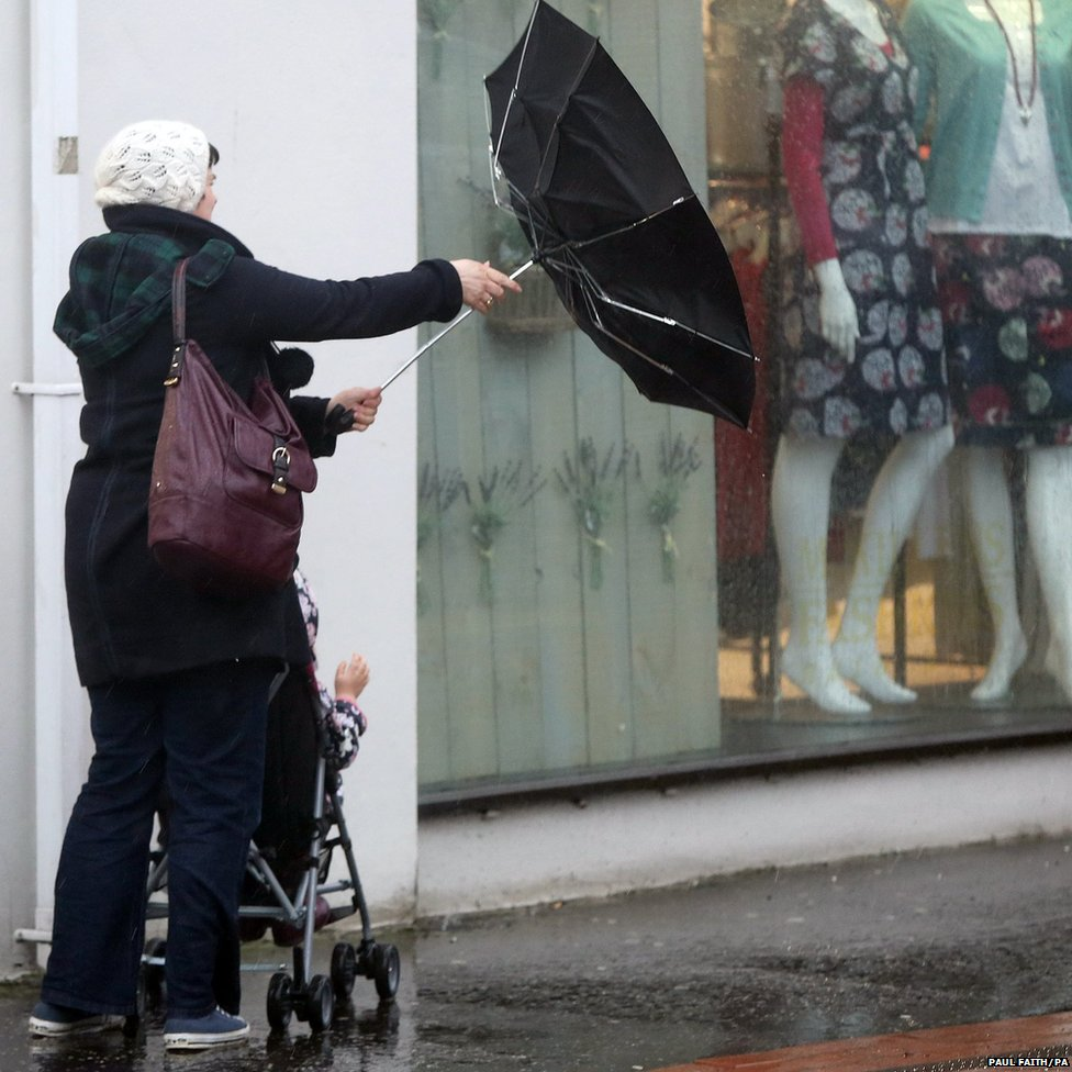 A woman struggles with an umbrella during high winds in Ballymena, County Antrim, as the Met Office issue two severe weather warnings for Northern Ireland
