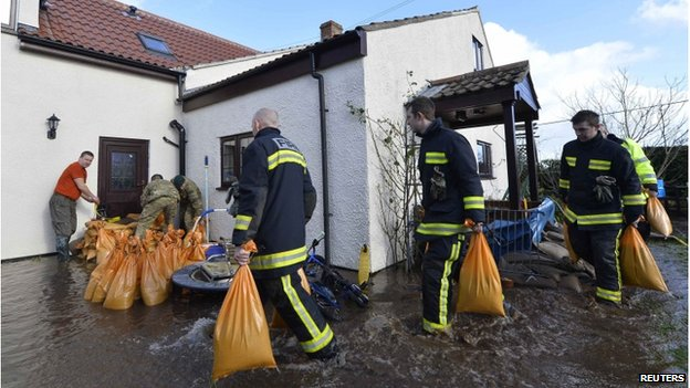 Firefighters and soldiers pile sandbags at the door of a home which is surrounded by flood water