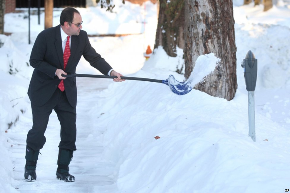 A man clears his sidewalk in Winchester, Virginia on 14 February 2014
