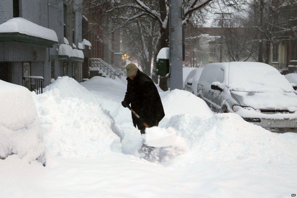 A man shovels his sidewalk in Buffalo, New York, on 14 February 2014