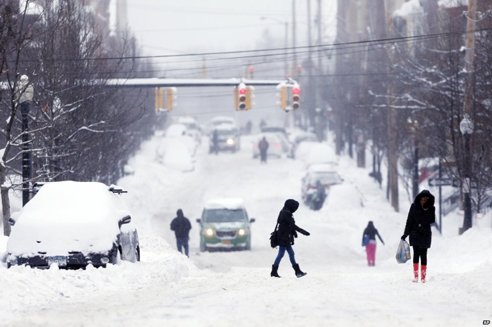 Pedestrians walk along a snow-covered street in Albany, New York on 14 February 2014