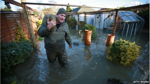 A man carries a sandbag on his shoulder through a flooded garden