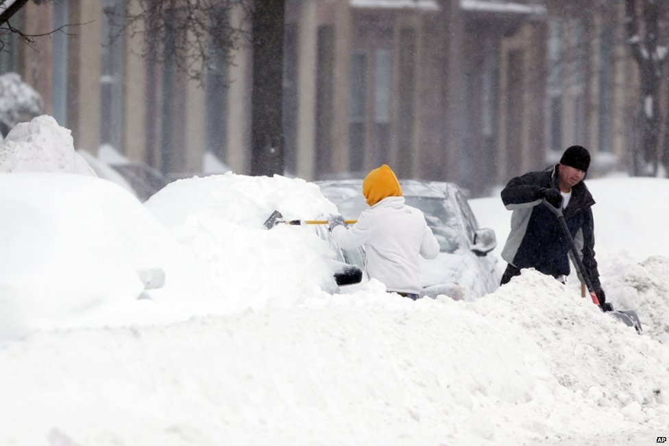 People dig out vehicles after overnight snow in Albany, New York on 14 February 2014