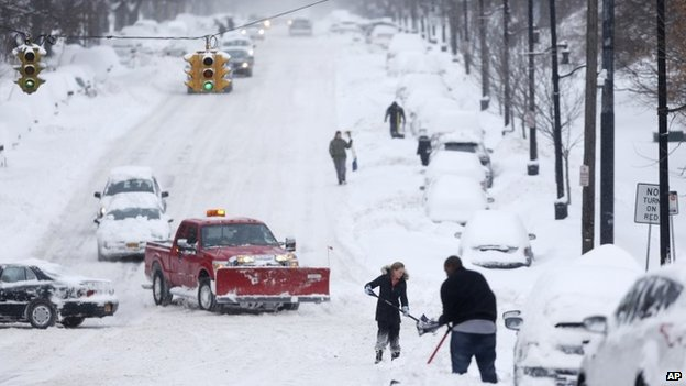 People dig out vehicles after overnight snow in Albany, New York, on 14 February 2014