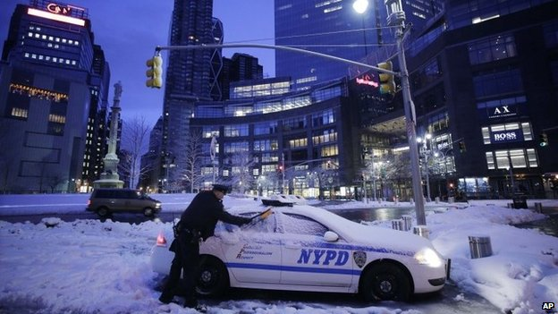 A New York City police officer scrapes snow and ice from his patrol car on 14 February 2014