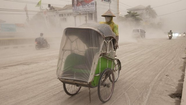 A man wears a mask as he rides a becak