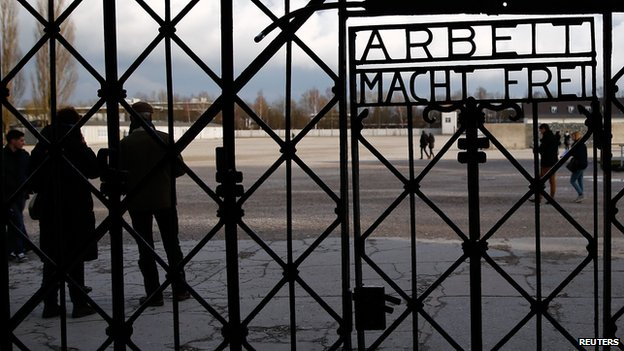 "Visitors walk past the main gate with the sign ""Arbeit macht frei"" (work sets you free) at the former concentration camp in Dachau near Munich January 25, 2014"