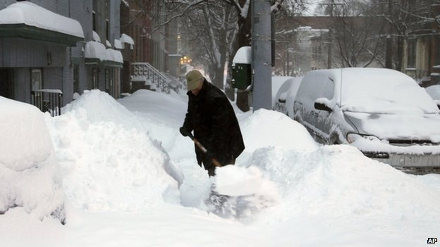 A man shovels his sidewalk in Buffalo, New York, on 14 February 2014
