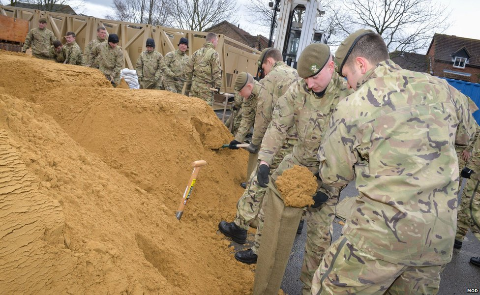 Soldiers of 2nd Battalion The Royal Welsh fill sandbags as they help protect properties in Gloucester.