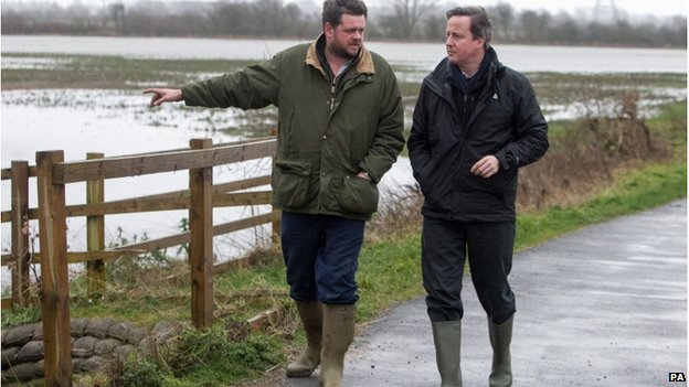 David Cameron speaks to farmer Tim Hook as they walk along a road next to flooded land