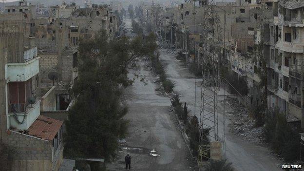 A man walks along a conflict-ravaged street in Deir el-Zor in eastern Syria, 14 February 2014