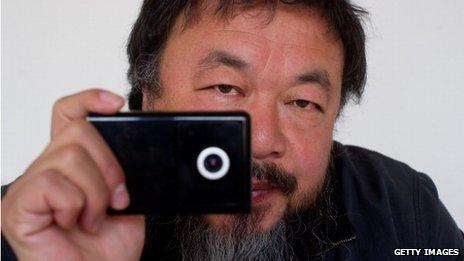 Ai Weiwei, holding a webcam