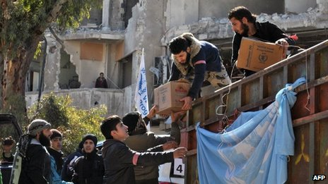 Rebel fighters help unload aid food during a UN-led humanitarian operation in the besieged Syrian city of Homs