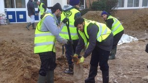 Volunteers fill sandbags