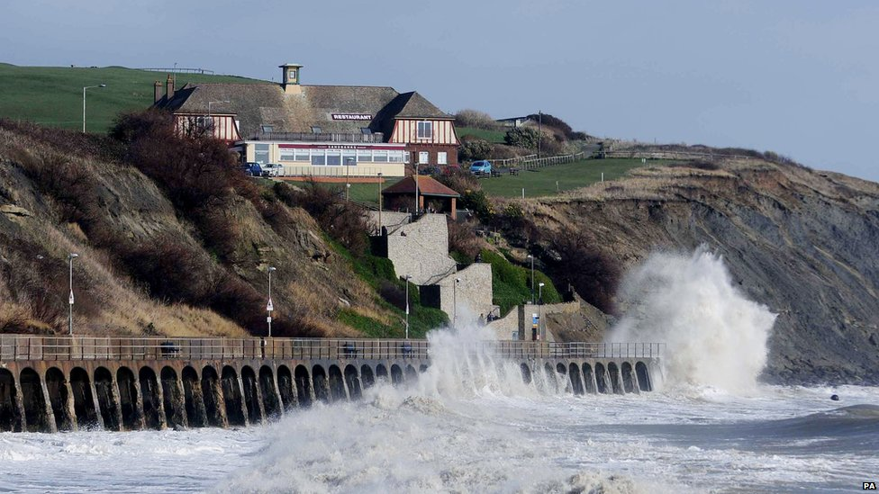 Waves break below the East Cliff Pavillion in Folkestone during high tide.