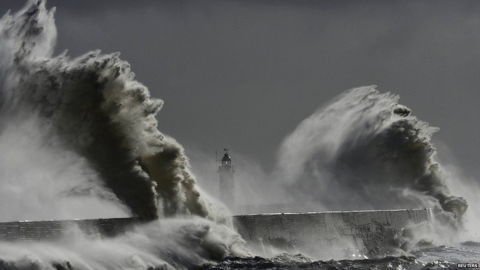 Large waves hit the lighthouse and harbour at high tide at Newhaven in Sussex