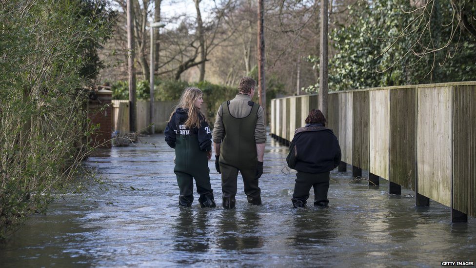 Residents walk along a flooded street in Henley-on-Thames