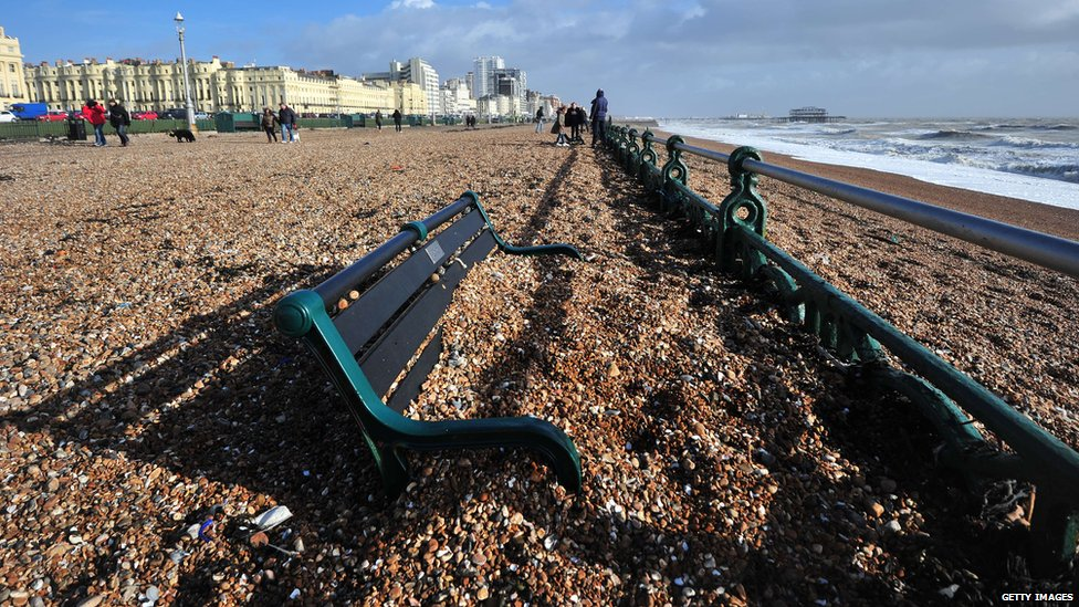 Pebbles blown up from the beach engulf a bench on Hove promenade, in Brighton