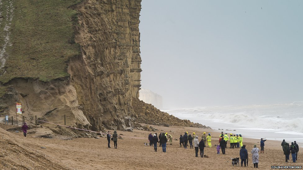 Emergency services and on-lookers after a cliff collapsed at West Bay, in Dorset