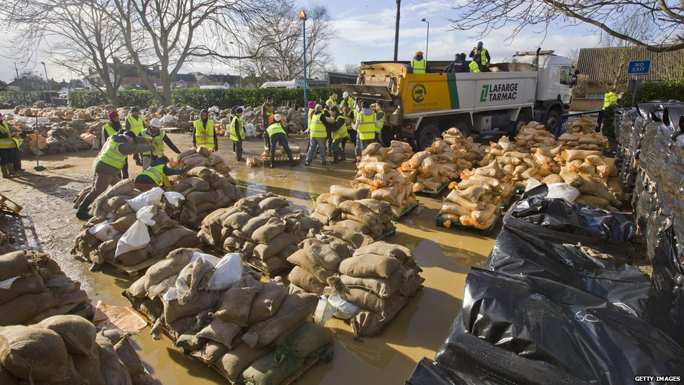 Volunteers and charities fill sandbags before they are distributed in Egham, west of London.