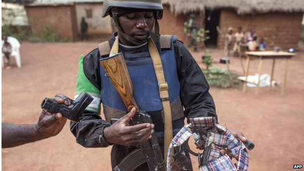 A soldier shows amulets and a toy gun the troops found during an operation in the Boy-rabe neighbourhood of Bangui on 15 February