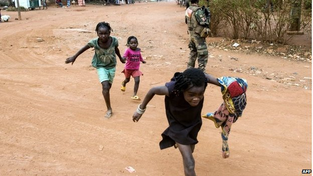Children take cover as gunfire breaks out during the operation to disarm militia and capture a senior militia leader