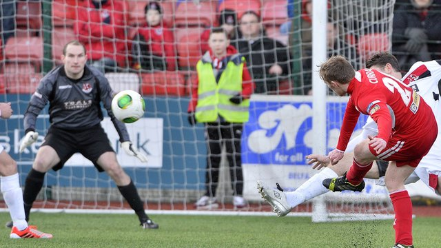 Cliftonville's Chris Curran scores past Crusaders Sean O'Neill