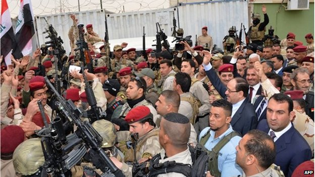 A handout picture released by the Iraqi Prime Minister's media office shows Nouri al-Maliki greetings soldiers as he arrives in the capital of Anbar province, Ramadi