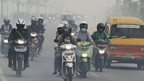 Motorists ride in the haze from forest fires in Indonesia's Riau province (27 June 2013)
