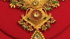 Example of Indian gold jewellery (ornate necklace with green jewels)