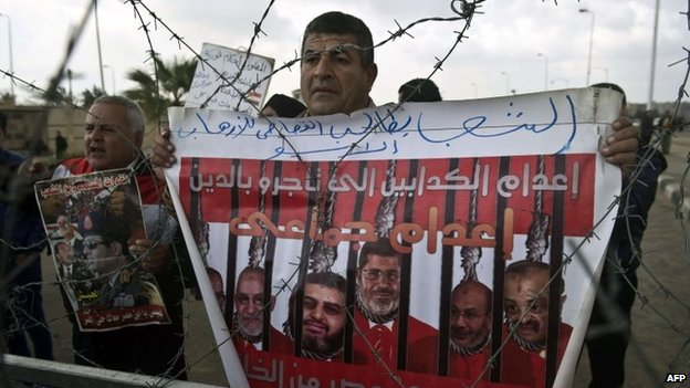 A pro-military Egyptian holds a poster behind barbed wires