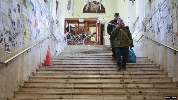 An anti-government protester leaves the city hall in Kiev.