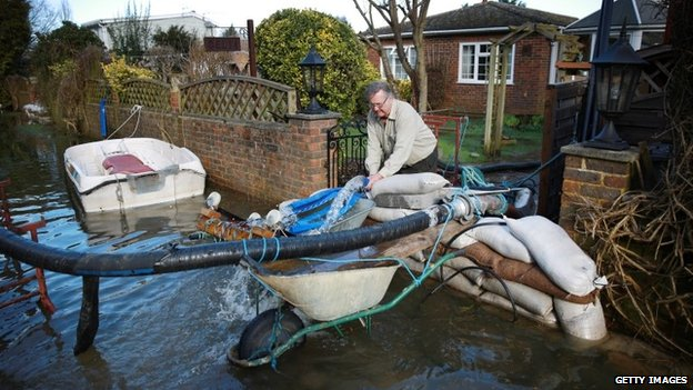 A man adjusts pipes that are removing flood water from his property in Chertsey