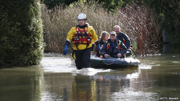 Volunteers from the International Rescue Corps help a couple evacuate from a flooded house in Chertsey