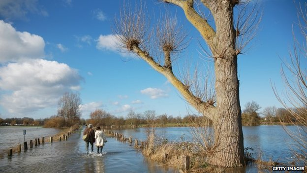 A couple walk through flood water on Chertsey Meads, in Chertsey,