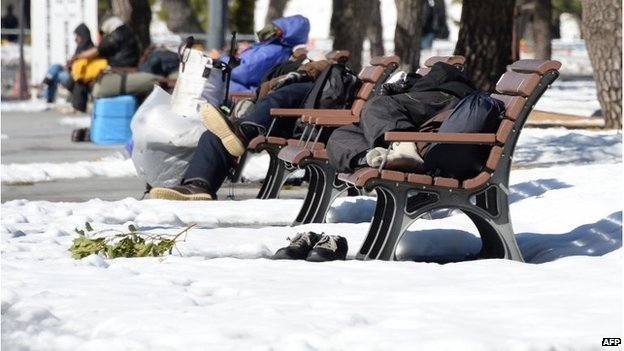Homeless men take naps on benches at a park in Tokyo on February 16