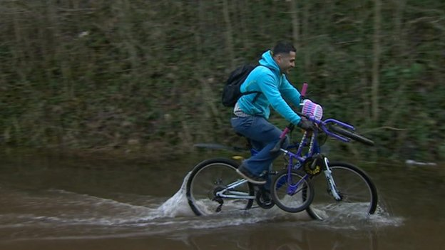 Man on bicycle on flooded cycle path