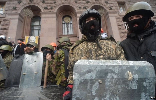Maidan self-defence activists guard the building to prevent it during their confrontation in Kiev on February 16