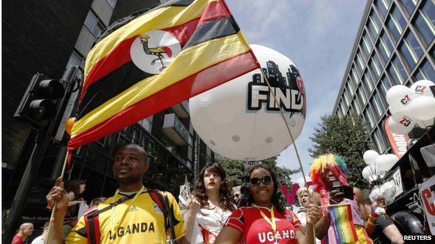 Participants waving a Uganda flag and wearing Uganda sports shirts participate in London's annual Pride London parade in June 2013