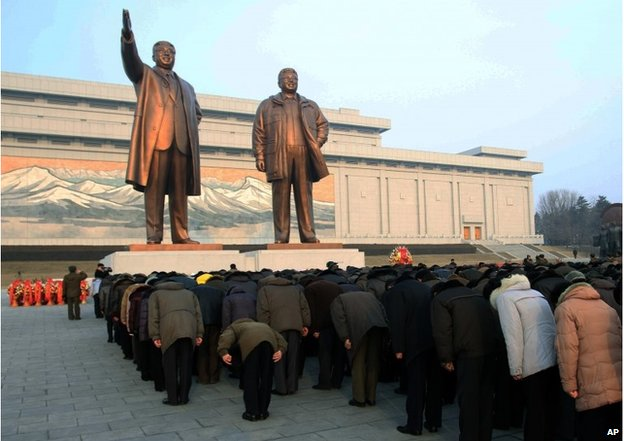 Crowds bow to the statues of North Korea's late leader Kim Jong-il, right, and his father Kim Il-sung near Pyongyang, Feb. 16