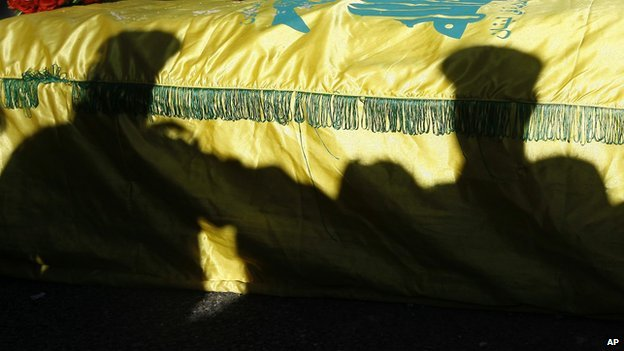 The shadow of Hezbollah fighters are silhouetted on the coffin of their commander Ali Bazzi, who was killed in Syria during a battle against rebels, during his funeral procession, in the southern port city of Sidon, Lebanon, on 9 December 2013.