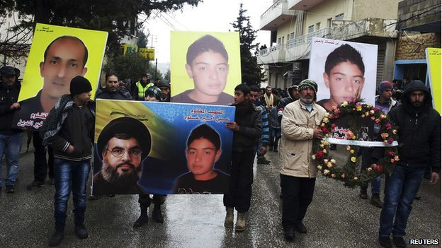 Friends and family members of victims killed in a car bomb attack hold a wreath along with their pictures during a funeral in the Shia town of Hermel on 3 February 2014.