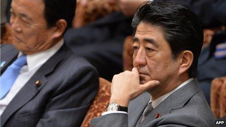 Japanese Prime Minister Shinzo Abe sitting next to Finance Minister Taro Aso