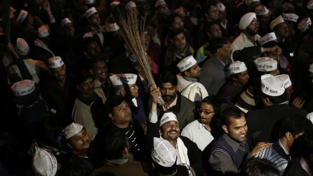 "A supporter of Delhi""s Chief Minister Arvind Kejriwal, chief of the Aam Aadmi (Common Man) Party (AAP), holds a broom, the party symbol, at the party headquarters in New Delhi February 14, 2014"