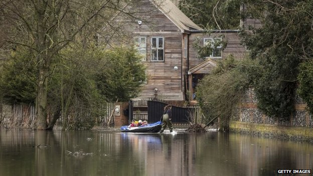A woman uses a dinghy to transport her children from their flooded home in Hurley, Berkshire