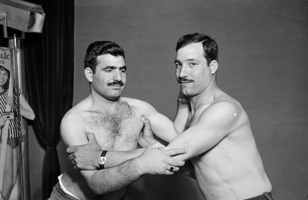 two men wrestle with their shirts off