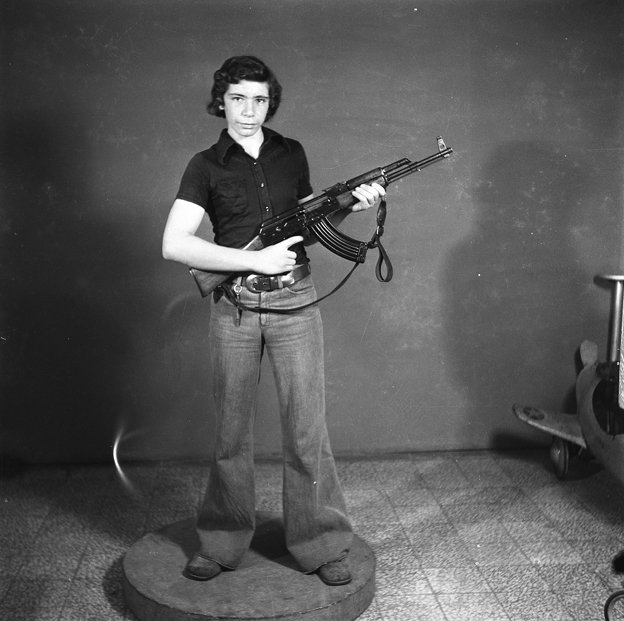 boy poses with automatic rifle